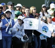 Kids holding signs to cheer on players at AT&T Pebble Beach Pro-Am