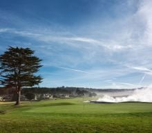 Wave crashing at the 18th hole at Pebble Beach