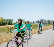 Youth Biking Along River