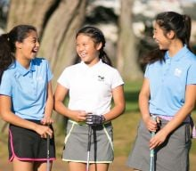 Three young women laughing on the golf course